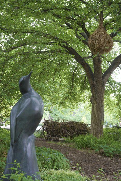 Sculpture of bird looking up at woven nest