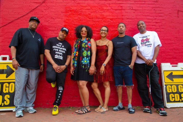 Musical group poses against red wall