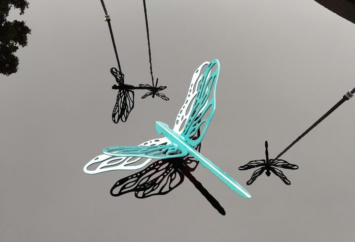 Dragonfly sculpture hovering over water