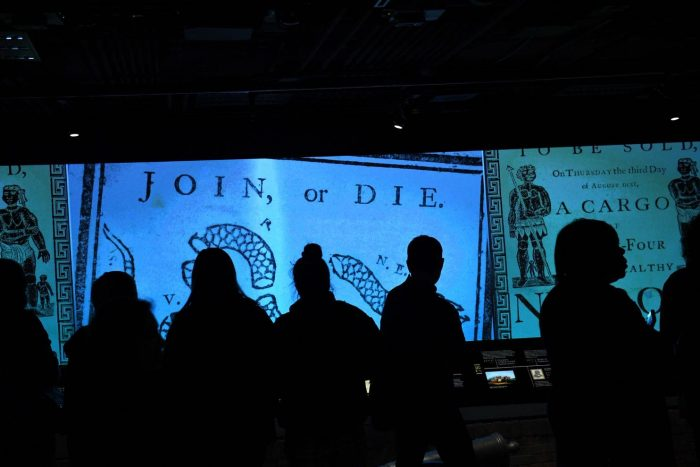 """Crowd silhouetted in front of """"Join or Die"""" case"""