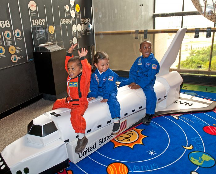 Three children playing on model of space shuttle