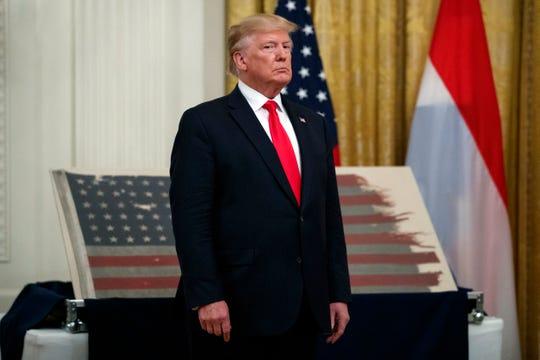 Trump standing before tatterred flag.
