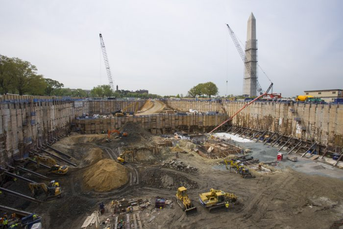 Construction site showing cranes and heavy equipment working on foundation.