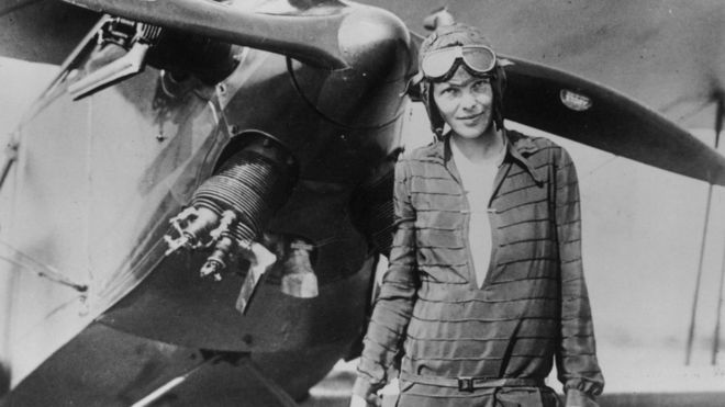 Old photo of Amelia Earhart with her plane