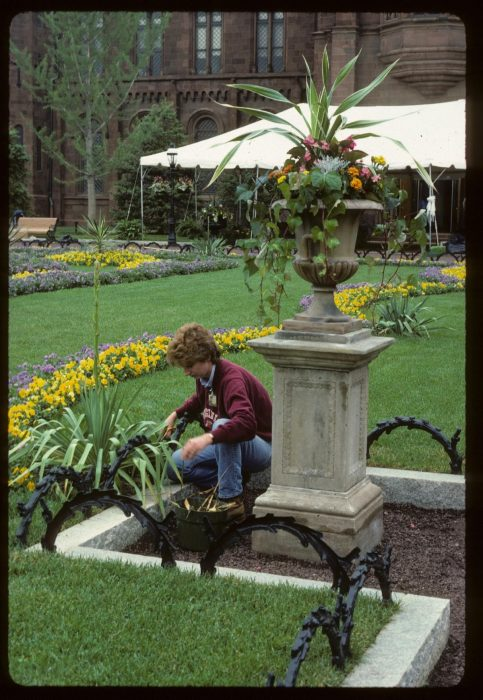 Young Barbara Faust planting flowers