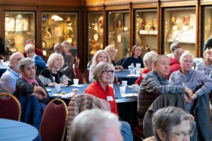 Volunteers at tables looking toward unseen speaker