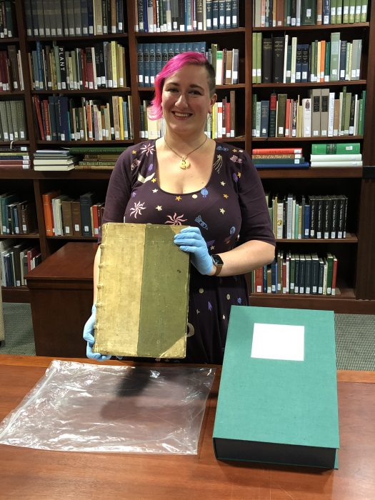 Alvis wearing gloves and holding rare book