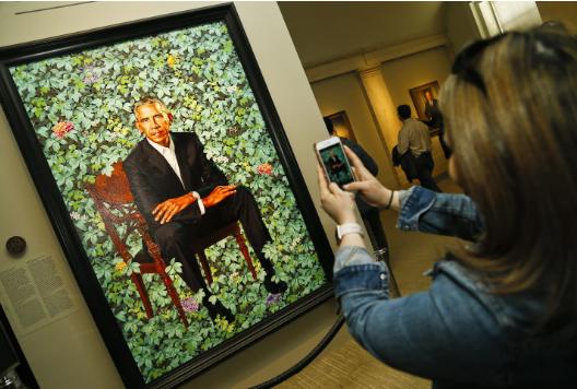 Woman taking photo of Obama portrait