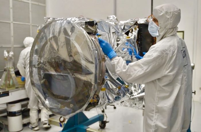 Scientists in clean room wearing masks work on TEMPO measuring instrument