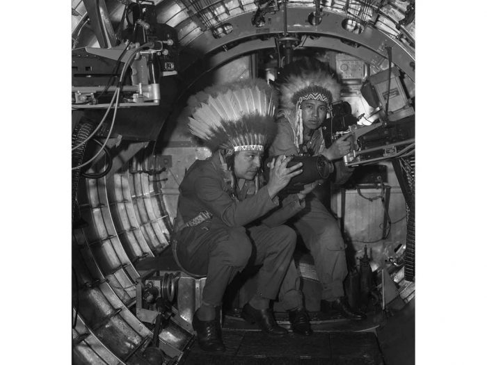 Horace Poolaw with feathered war bonnet inside WWI aircraft