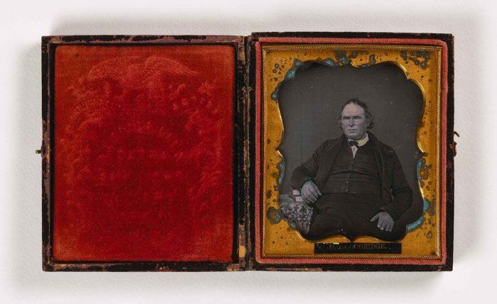 Portrait of man with books in red velvet case