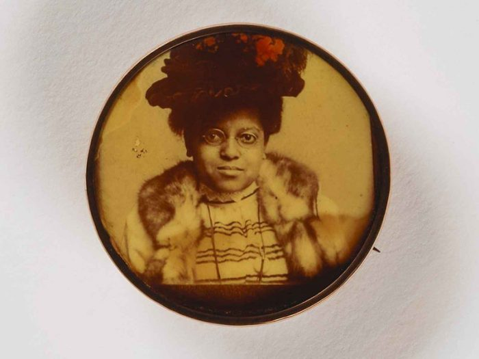 Portrait of African American woman wearing glasses and a fancy hat